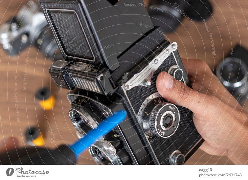 Durchführung der Reinigung von Vintage-Fotokamerafilmen Werkzeug Technik & Technologie Auge alt retro schwarz Antiquität Versammlung Hintergrund Bürste