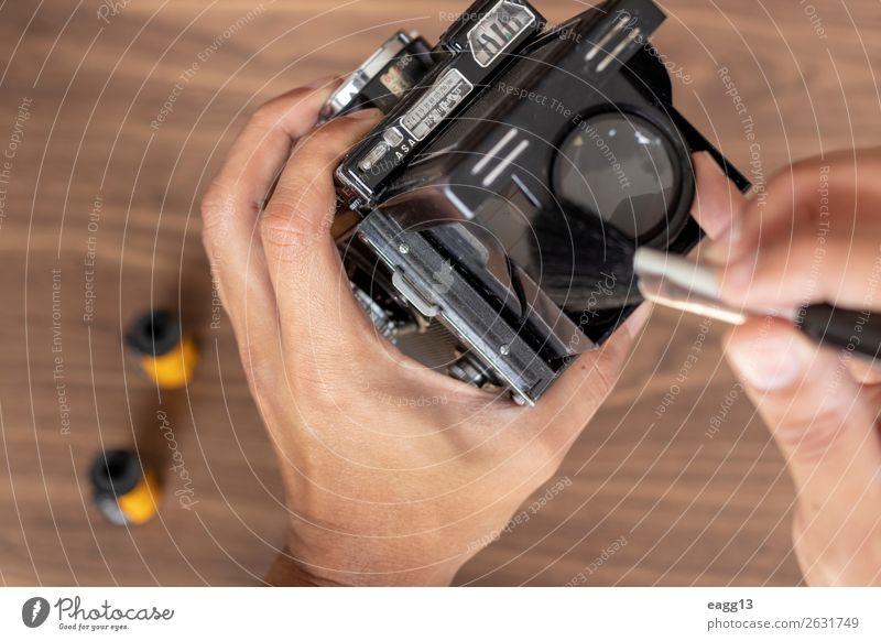Durchführung der Reinigung einer klassischen Fotokamera Werkzeug Technik & Technologie Auge alt retro schwarz Antiquität Versammlung Hintergrund Bürste