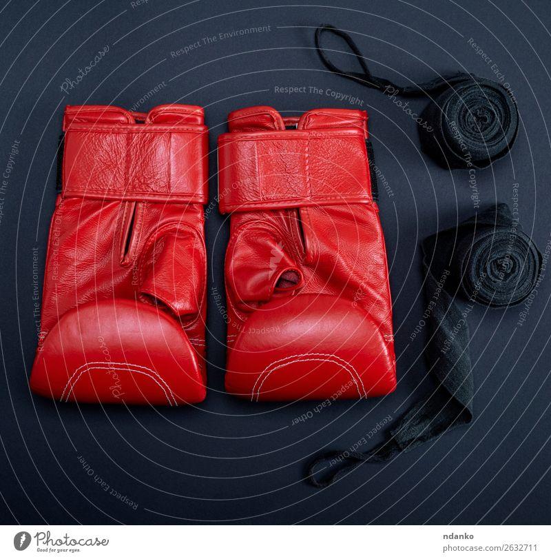rote Leder-Boxhandschuhe und eine schwarze Textilbinde Fitness Sport Handschuhe oben Schutz Farbe Konkurrenz Kreativität sportlich Hintergrund Kasten Boxer