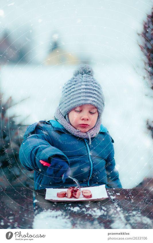 Junge isst gebratene Wurst beim Picknick im Winter im Freien. Wurstwaren Essen Lifestyle Freude Schnee Winterurlaub 3-8 Jahre Kind Kindheit Schneefall Mütze
