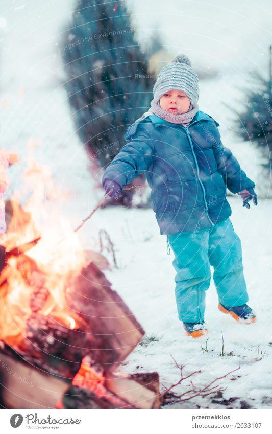 Junge spielt im Winter am Lagerfeuer im Freien einen Stock. Lifestyle Freude Glück Freizeit & Hobby Schnee Garten Kind Mensch 1 3-8 Jahre Kindheit Schneefall
