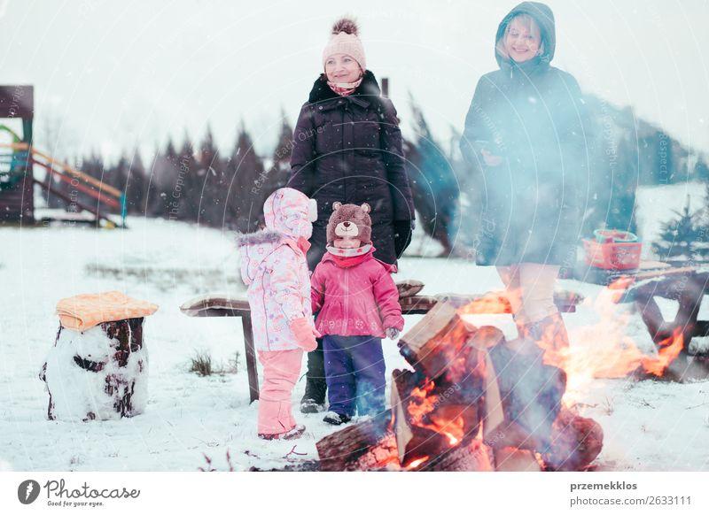 Die Familie, die Zeit zusammen verbringt, versammelt sich am Lagerfeuer. Lifestyle Freude Glück Freizeit & Hobby Winter Schnee Winterurlaub Garten Kind Mädchen