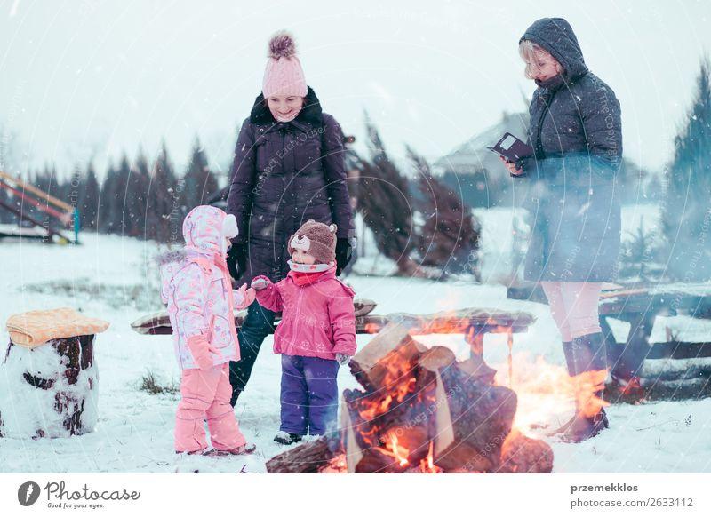 Die Familie, die Zeit zusammen verbringt, versammelt sich am Lagerfeuer. Lifestyle Freude Glück Freizeit & Hobby Winter Schnee Winterurlaub Garten Kind Mensch