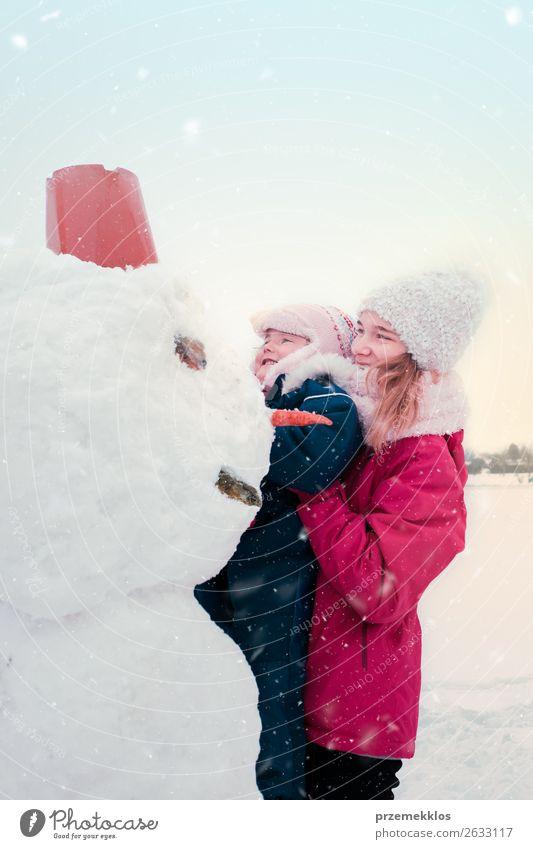 Mädchen und ihre kleine Schwester machen einen Schneemann. Lifestyle Freude Glück Winter Winterurlaub Kind Mensch Junge Frau Jugendliche Erwachsene