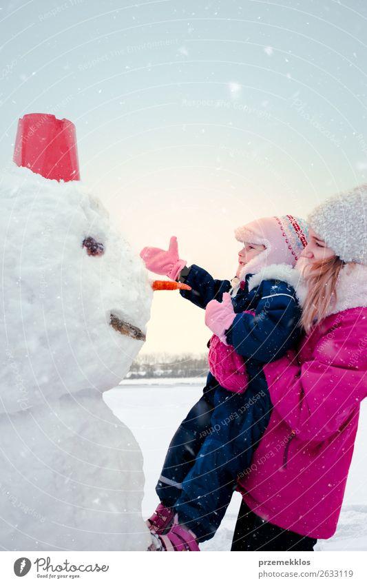 Mädchen und ihre kleine Schwester machen einen Schneemann. Lifestyle Freude Glück Winter Winterurlaub Kind Mensch Junge Frau Jugendliche