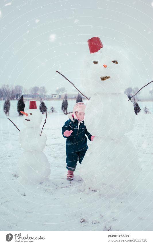 Kleines Mädchen macht einen Schneemann Lifestyle Freude Glück Winter Kind Mensch 1 3-8 Jahre Kindheit Schneefall Bekleidung genießen machen klein niedlich weiß