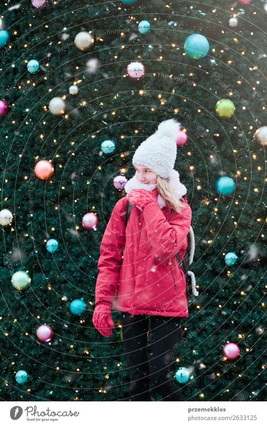 Junges Mädchen steht vor dem großen Weihnachtsbaum. Lifestyle Freude Winter Schnee Dekoration & Verzierung Weihnachten & Advent Mensch Junge Frau Jugendliche