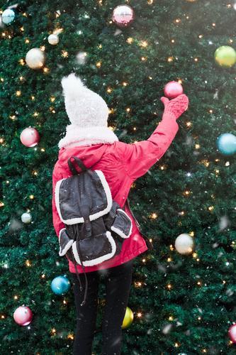 Junges Mädchen steht vor dem großen Weihnachtsbaum. Lifestyle Freude Winter Schnee Dekoration & Verzierung Weihnachten & Advent Mensch Junge Frau Jugendliche 1