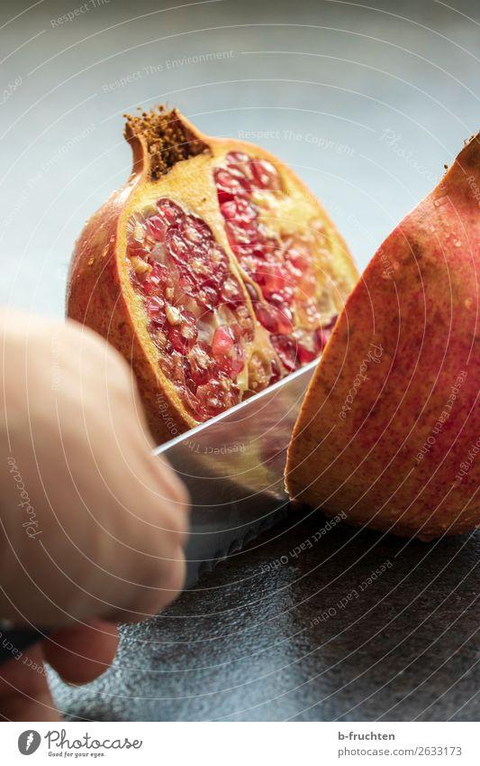 Granatapfel schneiden Frucht Bioprodukte Vegetarische Ernährung Gesunde Ernährung Hand Finger frisch Gesundheit rot Kerne Essen zubereiten Hälfte Messer