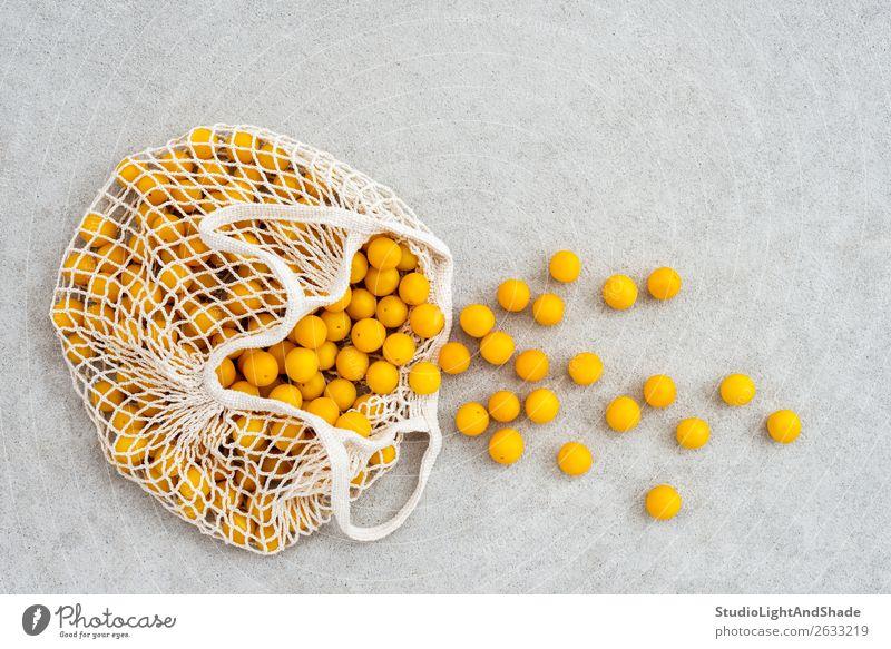 Viele gelbe Pflaumen in einer Netz-Einkaufstasche Lebensmittel Frucht Ernährung Lifestyle kaufen Sommer Gartenarbeit Natur Herbst Beton einfach frisch hell