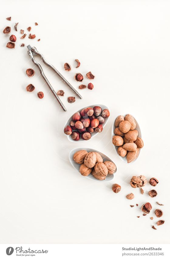 Nussknacker und Teller voller Nüsse Lebensmittel Ernährung Essen Bioprodukte Vegetarische Ernährung Diät Schalen & Schüsseln frisch Gesundheit natürlich braun