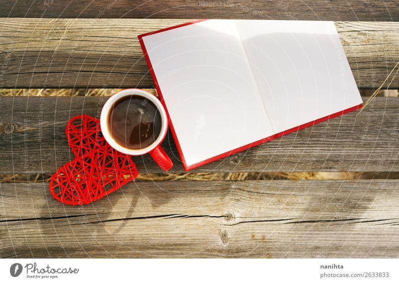 Rote Tasse mit Kaffee auf einer Holzbank im Freien am Morgen. Frühstück Getränk Heißgetränk Tee Becher Winter Buch lesen Herbst Wärme Papier Herz frisch
