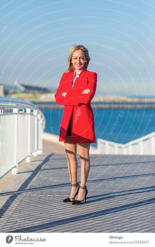 Erwachsene Frau, die auf einer Brücke neben dem Meer steht. Lifestyle Business Fotokamera feminin Arme Horizont Hemd Rock Jacke Schuhe Damenschuhe blond Lächeln
