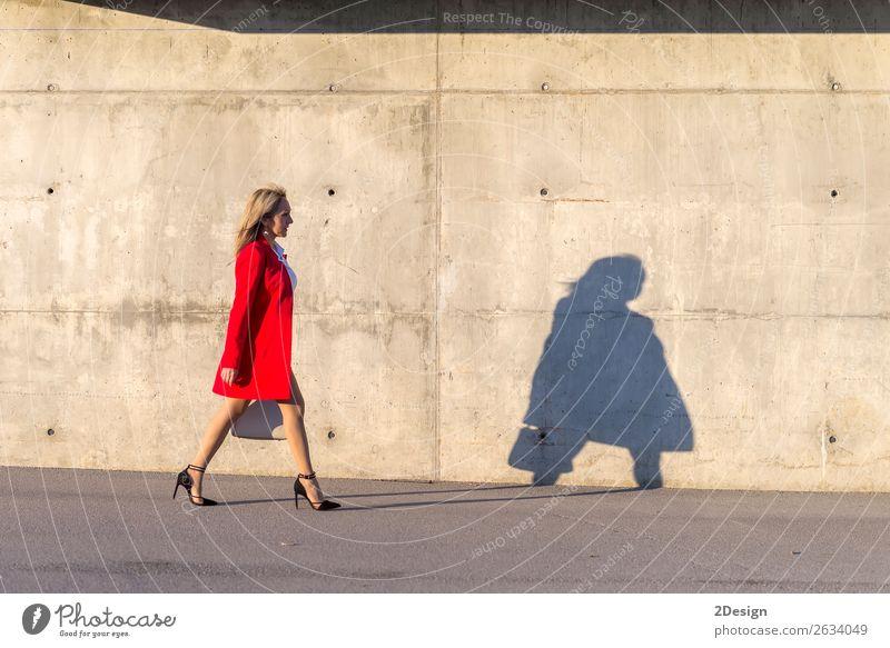 Blonde Frau in roter Jacke, die auf der Straße geht. Lifestyle schön Business feminin Erwachsene Hemd Rock Schuhe Damenschuhe blond schwarz weiß Geschäftsfrau