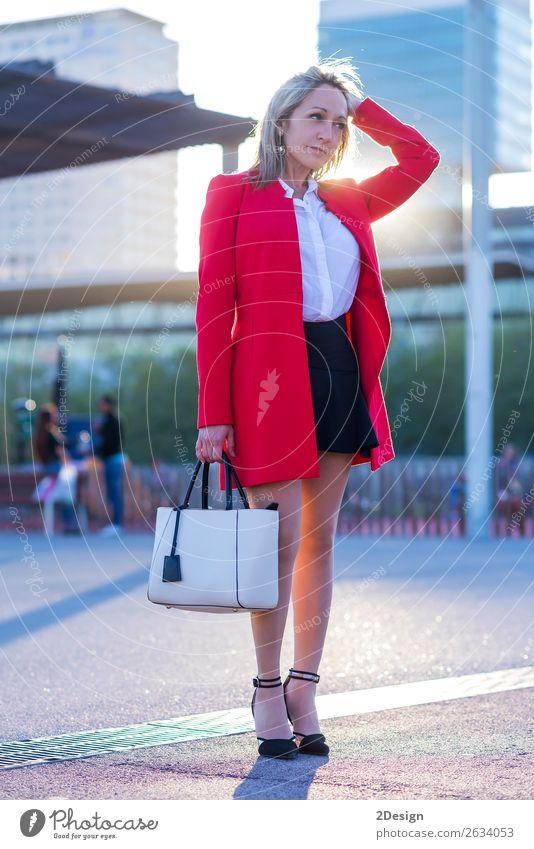 Elegante blonde Frau, die auf der Straße steht und eine rote Jacke trägt. elegant Stil schön Mensch feminin Erwachsene Mode Hemd Rock Schuhe Damenschuhe stehen