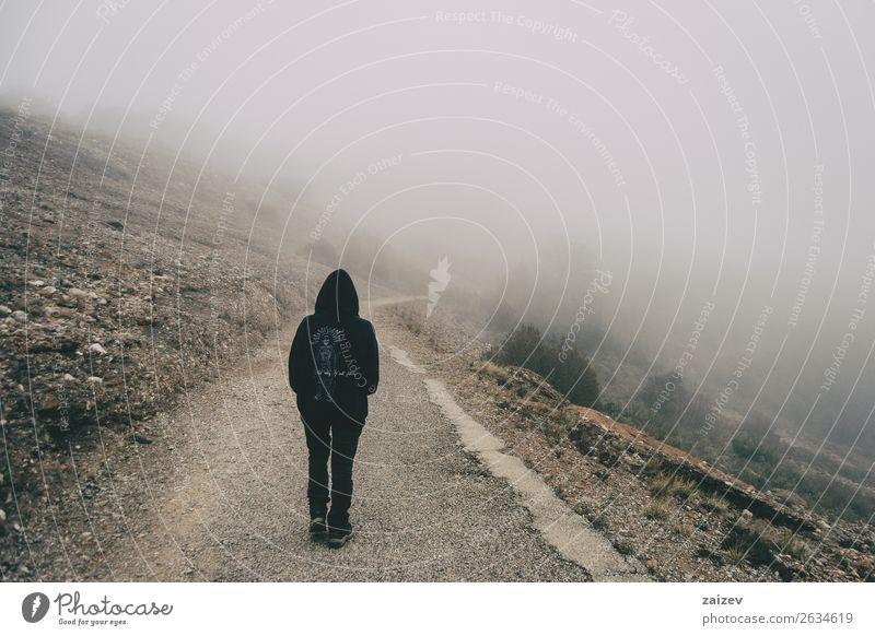 Mädchen, das auf einer Bergstraße mit viel Nebel läuft. Lifestyle schön Ferien & Urlaub & Reisen Tourismus Ausflug Abenteuer Freiheit Berge u. Gebirge wandern