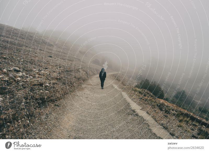 Mädchen geht auf dem Rücken auf einer Bergstraße mit viel Nebel Lifestyle schön Ferien & Urlaub & Reisen Tourismus Ausflug Abenteuer Freiheit Berge u. Gebirge