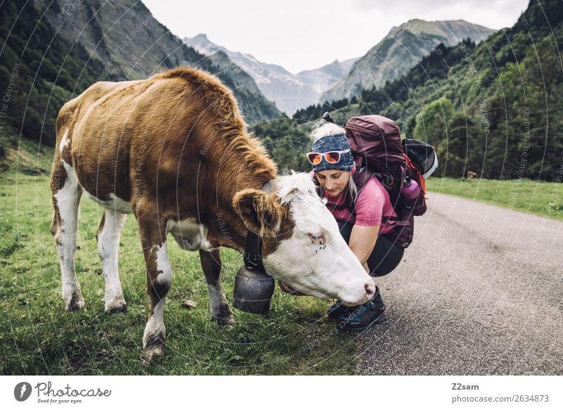 Junge Frau beim Wandern mit Kuh Lifestyle wandern feminin Jugendliche 18-30 Jahre Erwachsene Natur Landschaft Wiese Alpen Berge u. Gebirge Sonnenbrille