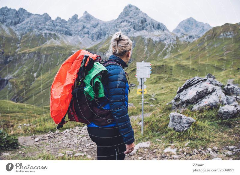 Junge Frau auf Alpenüberquerung Abenteuer wandern Jugendliche 18-30 Jahre Erwachsene Natur Landschaft Berge u. Gebirge daunenjacke Rucksack regenhülle blond