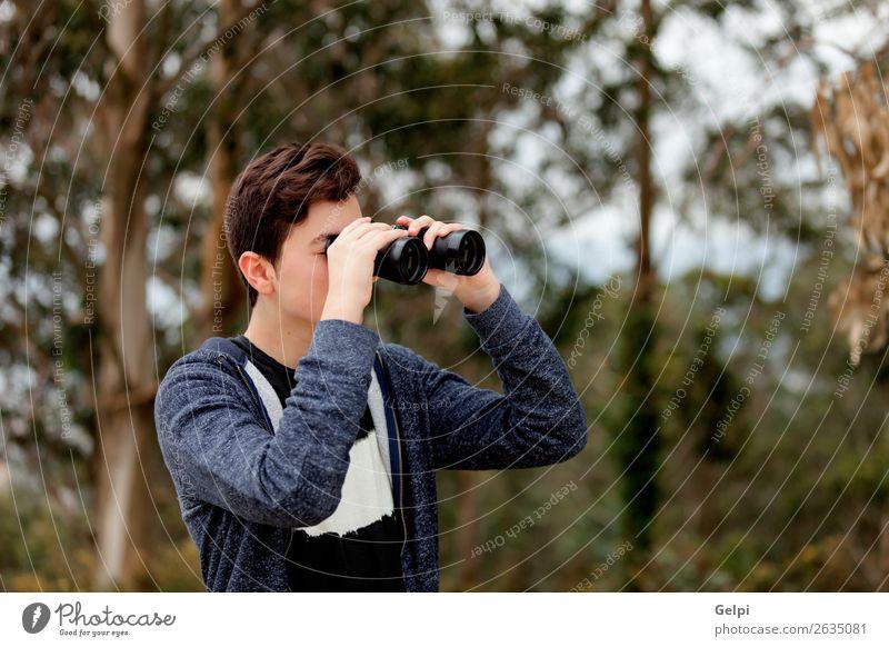 Teenager-Typ, der mit einem Fernglas aussieht. Lifestyle Freude Glück Freizeit & Hobby Sommer Kind Mensch Junge Mann Erwachsene Kindheit Jugendliche Hand Baum