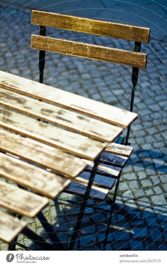 Tisch und Stuhl Straßencafé Klapptisch Klappstuhl Möbel Pflastersteine Bürgersteig Café Farbfoto Außenaufnahme Nahaufnahme Detailaufnahme Kunstlicht Licht