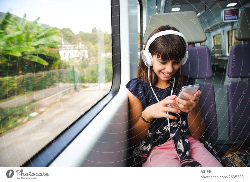 Kleines Mädchen mit Kopfhörer und Smartphone im Zug unterwegs Freude Glück schön Freizeit & Hobby Ferien & Urlaub & Reisen Ausflug Musik Kind Headset PDA