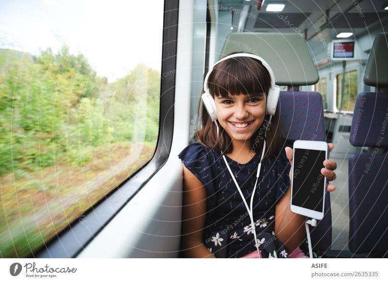 Sie ist glücklich mit ihrem Smartphone, das mit dem Zug fährt. Freude Glück schön Freizeit & Hobby Ferien & Urlaub & Reisen Ausflug Musik Kind Headset PDA
