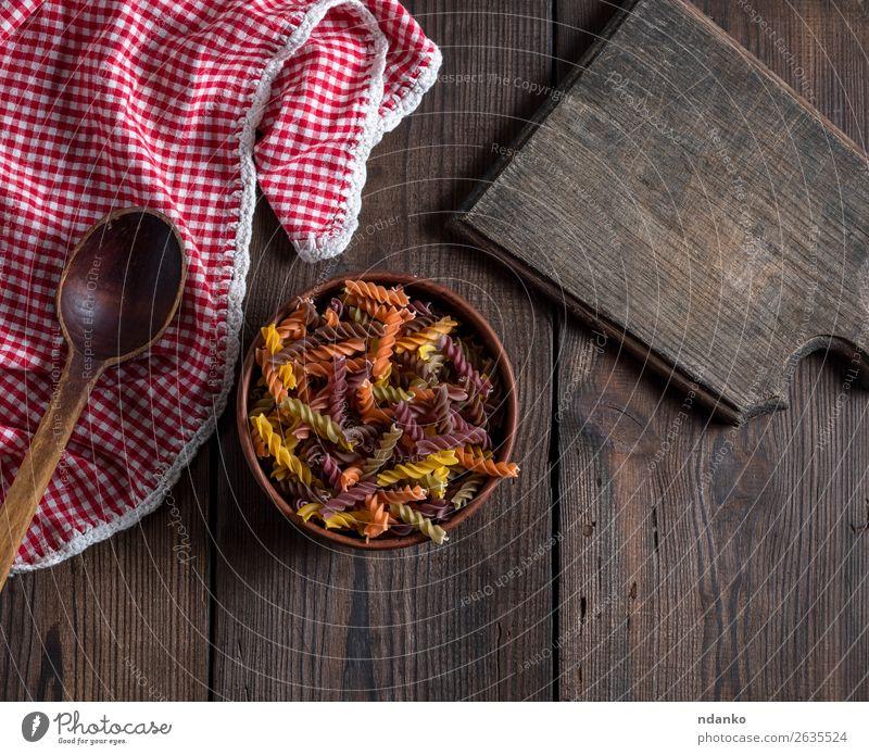 Rohteigwaren in brauner Tonschale auf Holztisch Ernährung Diät Schalen & Schüsseln Löffel gelb rot Farbe Tradition farbenfroh Essen zubereiten Speise trocknen