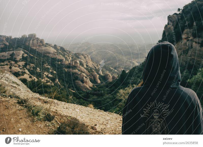 Mädchen auf dem Rücken mit Kapuze, die auf eine Berglandschaft blickt. Lifestyle schön Erholung Ferien & Urlaub & Reisen Tourismus Ausflug Abenteuer Freiheit