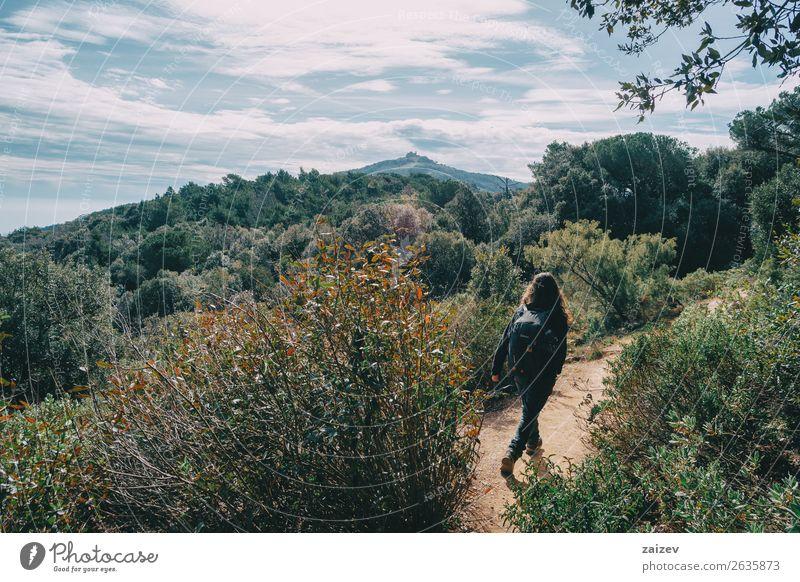 Frau, die an einem sonnigen Tag in der Ferne auf einem Pfad zwischen Bergen wandert Lifestyle Freude Glück Freizeit & Hobby Ferien & Urlaub & Reisen Tourismus