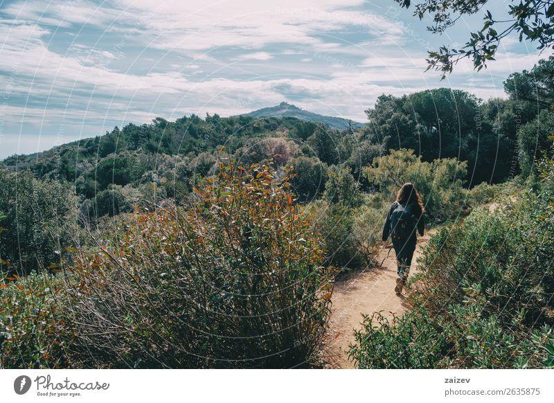 Frau, die in der Ferne auf einem Pfad zwischen den Bergen spazieren geht. Lifestyle Freude Glück Freizeit & Hobby Ferien & Urlaub & Reisen Tourismus Abenteuer