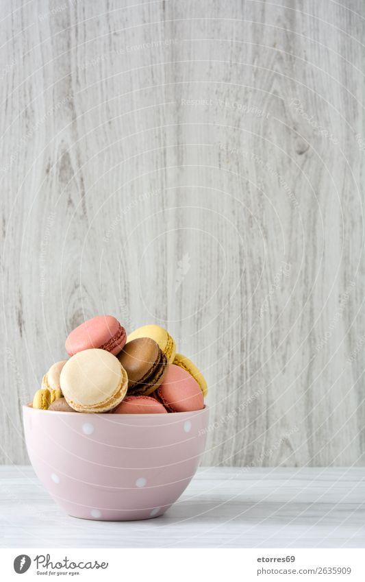 Bunte Makronen in einer Schleife auf weißem Holztisch Macaron Erdbeeren Zitrone Dessert Kaffee gelb Schokolade Konfekt Himbeeren Tradition Süßwaren
