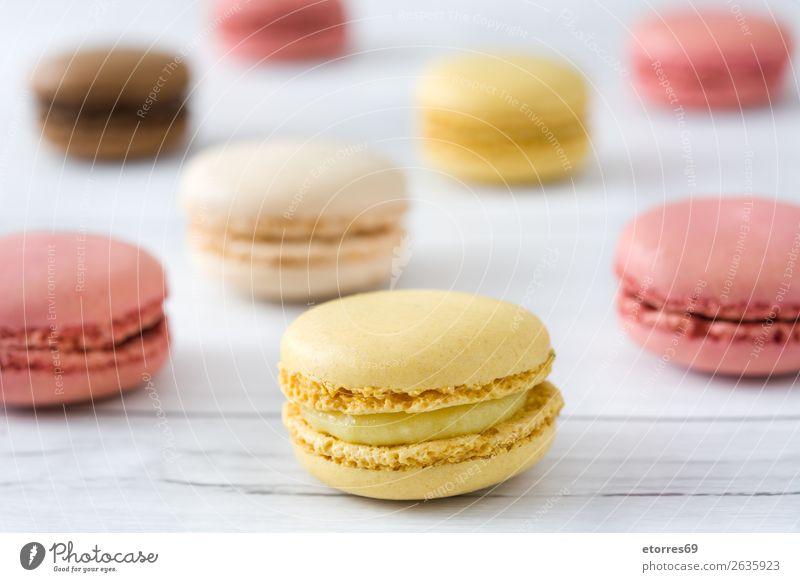 Bunte Makronen auf weißem Holztisch Macaron Erdbeeren Zitrone Dessert Kaffee gelb Schokolade Konfekt Himbeeren Tradition Süßwaren Bonbon Plätzchen ausstechen