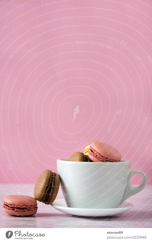 bunte Makronen aus einer Tasse auf rosa Hintergrund Macaron Erdbeeren Zitrone Dessert Kaffee gelb Schokolade Konfekt Himbeeren Tradition Süßwaren Biskuit