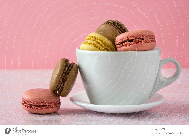 Bunte Makronen in einer Tasse auf rosa Hintergrund Macaron Erdbeeren Zitrone Dessert Kaffee gelb Schokolade Konfekt Himbeeren Tradition Süßwaren