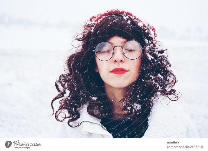 Junge und hübsche Frau, die einen verschneiten Wintertag genießt. Lifestyle Stil Glück Gesicht Wellness Leben Sinnesorgane ruhig Meditation Freizeit & Hobby