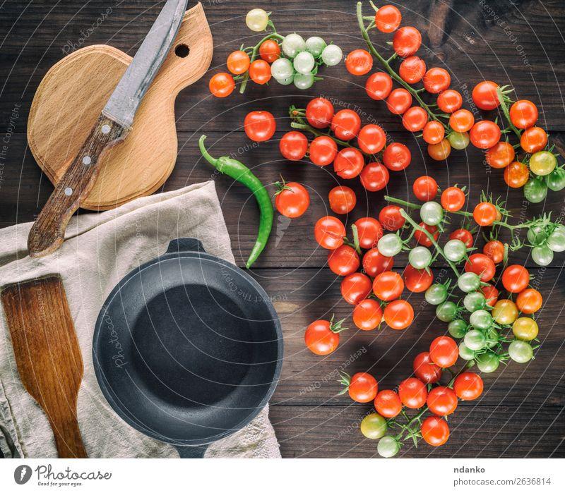 gusseiserne runde Bratpfanne und reife rote Kirschtomaten Gemüse Kräuter & Gewürze Vegetarische Ernährung Topf Messer Tisch Küche Holz Essen frisch klein