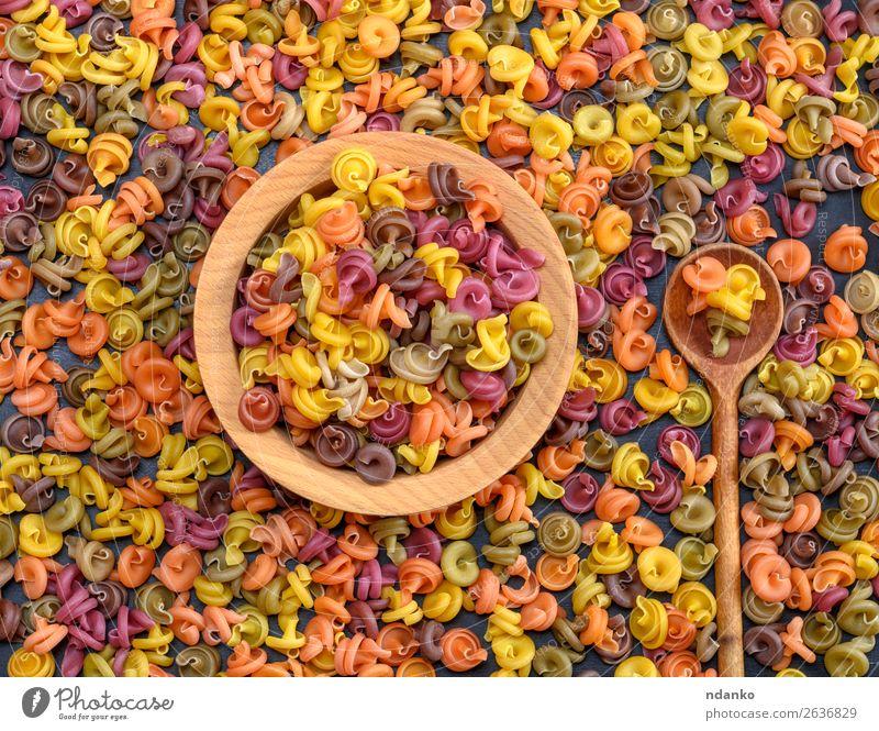 mehrfarbige spiralförmige Rohteigwaren-Fusilli in einer Holzschale Teigwaren Backwaren Ernährung Abendessen Diät Schalen & Schüsseln Löffel Essen frisch braun