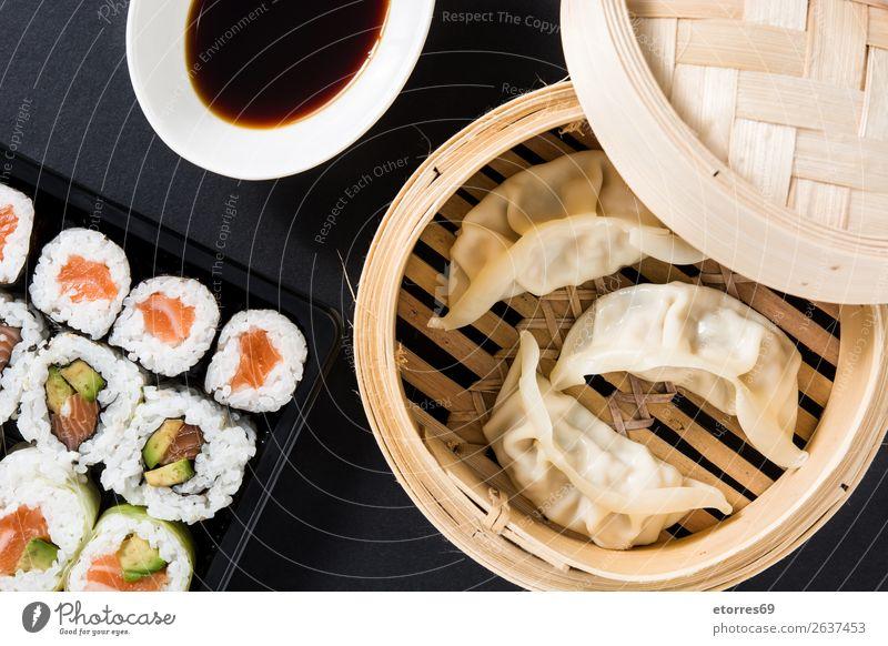 Knödel oder Gyoza auf traditionellem Dampfgarer und Sushi serviert. Gemüse Fisch maki Lebensmittel Gesunde Ernährung Foodfotografie Reis Brötchen Meeresfrüchte