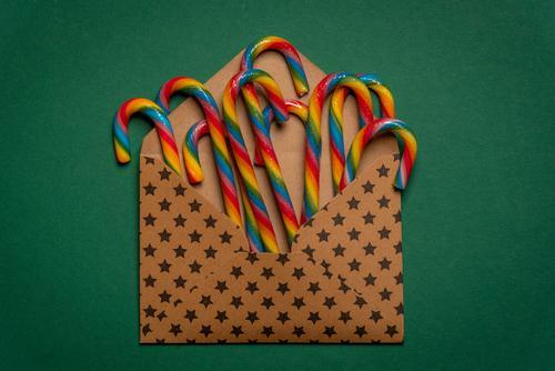 Mehrfarbige Zuckerstangen in einem offenen Umschlag Süßwaren Winter Feste & Feiern Weihnachten & Advent Geburtstag Papier braun grün Farbe Tradition