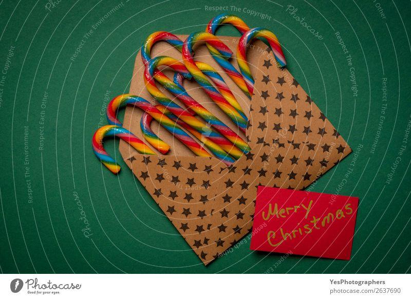Regenbogen-Kandiszuckerstangen und Frohe Weihnachten Nachricht Süßwaren Winter Feste & Feiern Weihnachten & Advent Silvester u. Neujahr Papier braun grün Farbe
