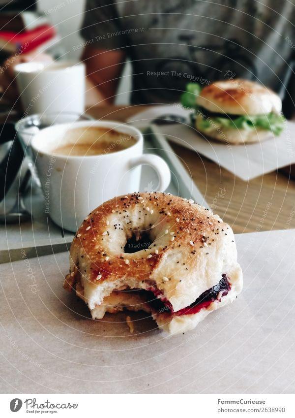 Two people having breakfast bagels in a cafe Lifestyle Junger Mann Jugendliche Erwachsene 1 Mensch genießen Bagel abgebissen Kaffee Café Frühstück Gesundheit