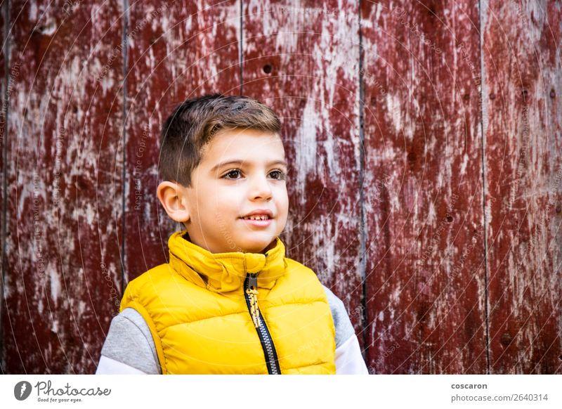 Kleines Kind mit einer gelben Weste vor einer alten roten Tür. Stil Glück schön Gesicht Mensch Baby Kleinkind Junge Kindheit 1 3-8 Jahre Mode Holz genießen