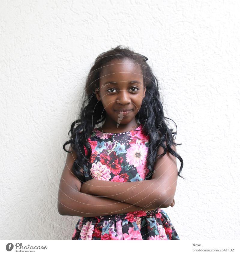 Gloria feminin Mädchen 1 Mensch Mauer Wand Kleid schwarzhaarig langhaarig Locken beobachten festhalten Lächeln Blick Zufriedenheit selbstbewußt Kraft
