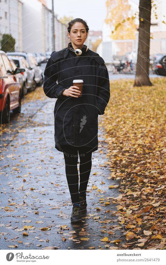 young woman walking along city street in autumn trinken Heißgetränk Kaffee Becher Lifestyle Stil Freizeit & Hobby Mensch feminin Junge Frau Jugendliche