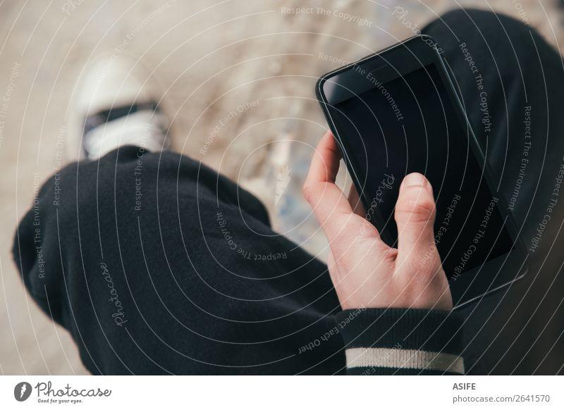 Smartphone in der Hand eines jungen Mannes Telekommunikation Telefon PDA Bildschirm Technik & Technologie Internet Erwachsene Jugendliche Finger Straße Jacke