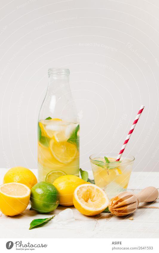 Frische hausgemachte Limonade auf weißem Hintergrund Frucht Diät Getränk Saft Flasche Sommer Tisch Blatt Holz Coolness frisch gelb grün Zitrone Kalk