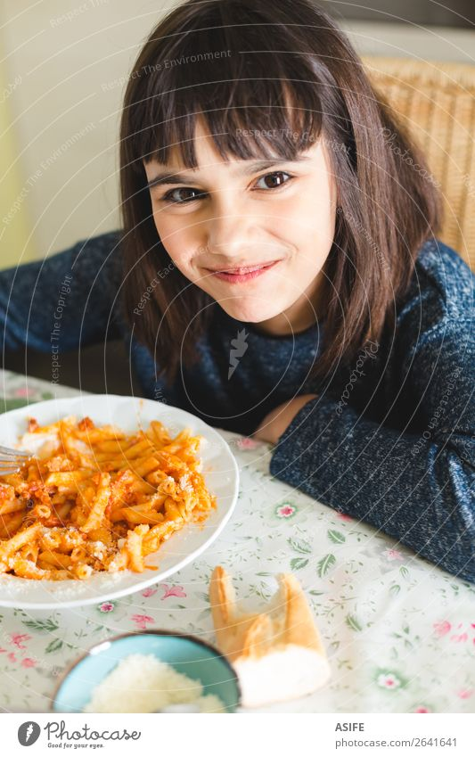Glückliches kleines Mädchen genießt Nudeln Käse Ernährung Essen Mittagessen Abendessen Gabel Freude schön Tisch Küche Kind Lächeln sitzen lecker niedlich