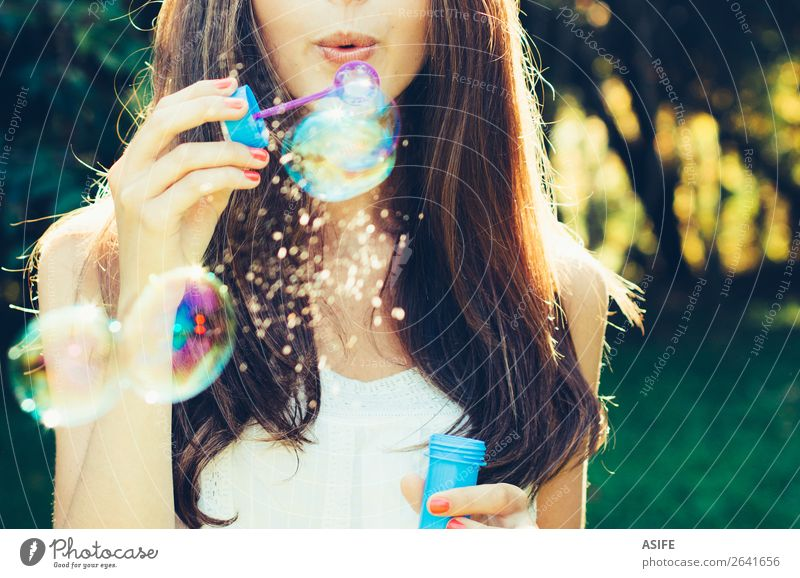 Mädchen, das Blasen bläst. Freude Glück schön Spielen Sommer Feste & Feiern Mensch Frau Erwachsene Lippen Natur Wärme Park träumen Fröhlichkeit weich grün