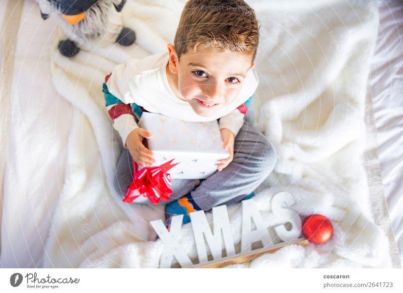 Littlr Kind am Weihnachtstag auf dem Bett mit einem Geschenk. Lifestyle Glück Gesicht Winter Haus Dekoration & Verzierung Raum Kinderzimmer Schlafzimmer
